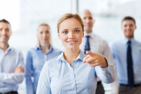 Stock photo: smiling businesswoman pointing finger on you