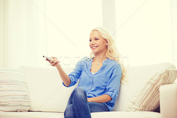 smiling young girl with tv remote control at home Stock photo © dolgachov