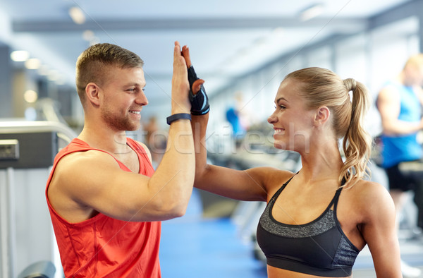 Stock photo: smiling man and woman doing high five in gym