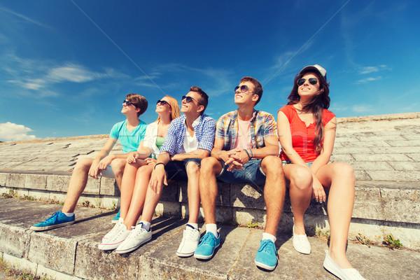 group of smiling friends sitting on city street Stock photo © dolgachov