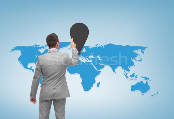 Stock photo: businessman pointing finger to mark on world map