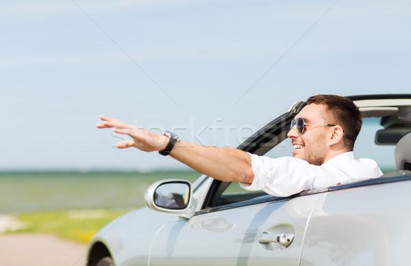 happy man driving cabriolet car and waving hand Stock photo © dolgachov