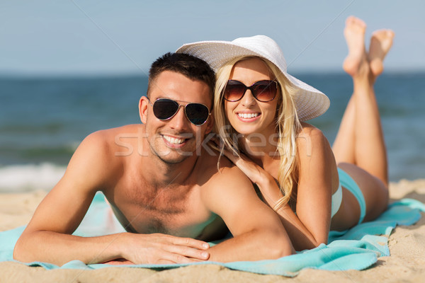happy couple in swimwear lying on summer beach Stock photo © dolgachov