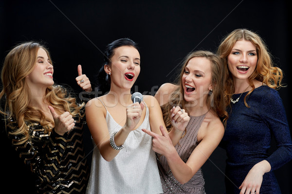 Stock photo: happy young women with microphone singing karaoke