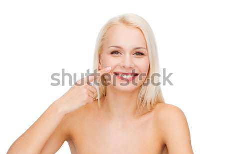 smiling woman with bare shoulders touching face Stock photo © dolgachov