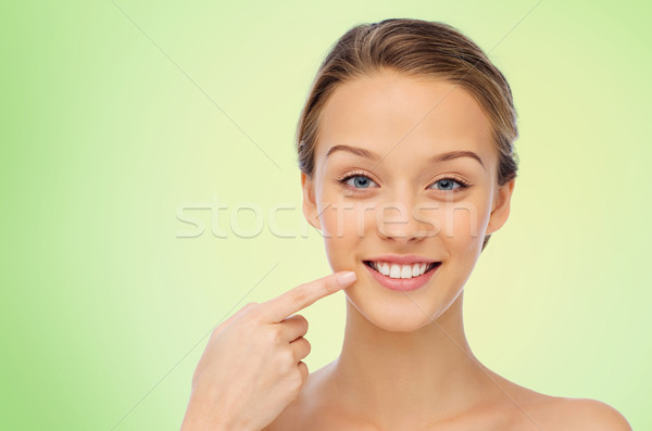 happy young woman pointing finger to her teeth Stock photo © dolgachov