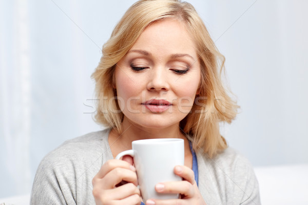 woman with cup of tea or coffee at home Stock photo © dolgachov
