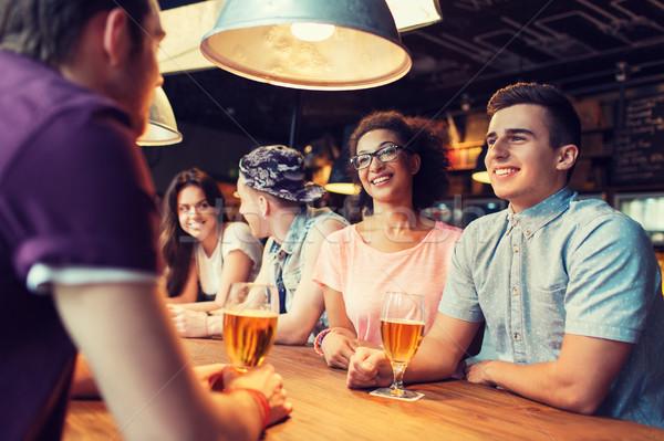 happy friends drinking beer and talking at bar Stock photo © dolgachov