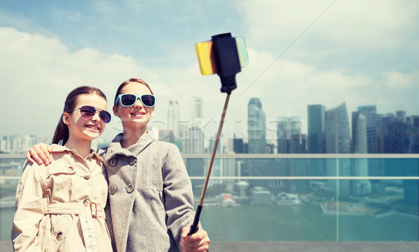 girls with smartphone selfie stick in singapore Stock photo © dolgachov
