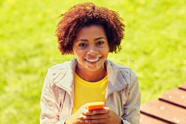 happy african young woman messaging on smartphone Stock photo © dolgachov