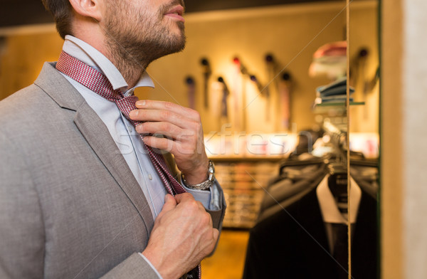 close up of man tying tie at clothing store mirror Stock photo © dolgachov