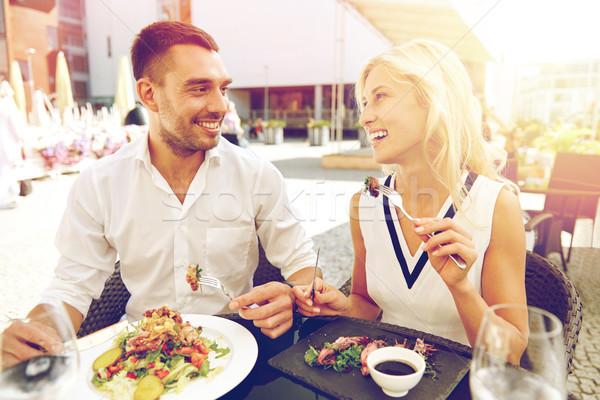happy couple eating dinner at restaurant terrace Stock photo © dolgachov