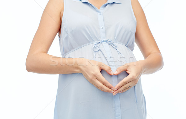 close up of pregnant woman making heart on belly Stock photo © dolgachov