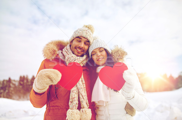 happy couple with red hearts over winter landscape Stock photo © dolgachov