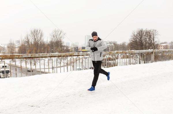 man with earphones running along winter bridge Stock photo © dolgachov