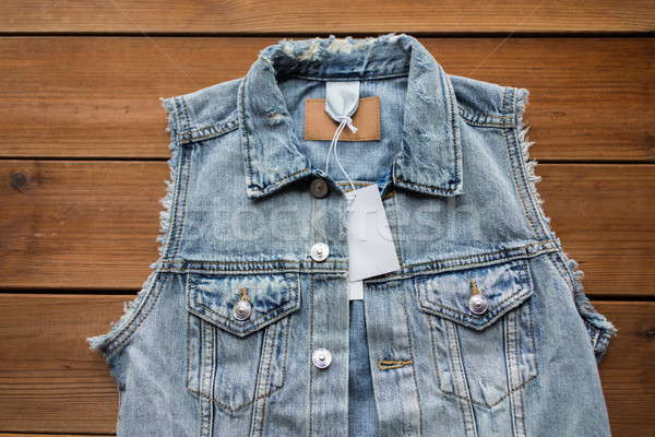 close up of denim waistcoat with price tag on wood Stock photo © dolgachov