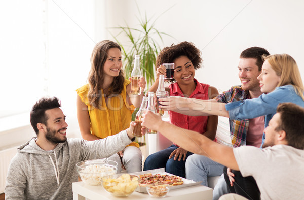 friends having party and clinking drinks at home Stock photo © dolgachov