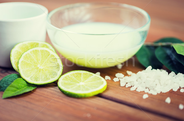 close up of body lotion in bowl and limes on wood Stock photo © dolgachov