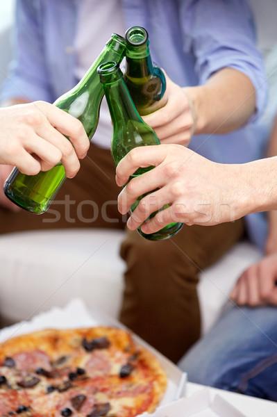 close up of friends clinking beer bottles at home Stock photo © dolgachov