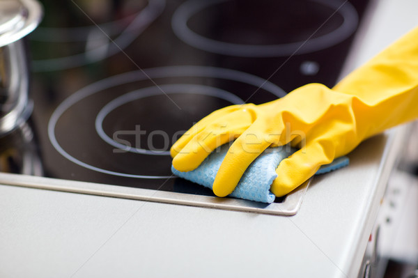 hand with rag cleaning cooker at home kitchen Stock photo © dolgachov