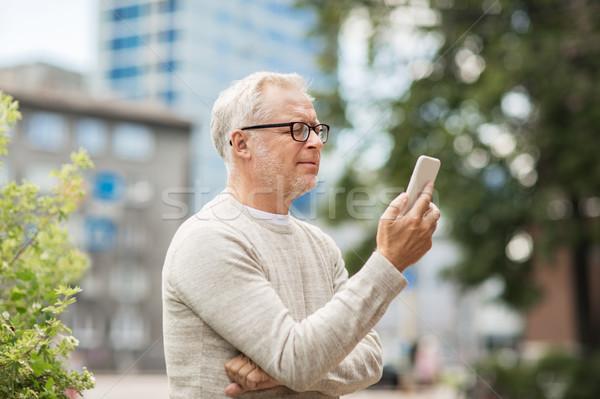 Idős férfi sms chat üzenet okostelefon város Stock fotó © dolgachov