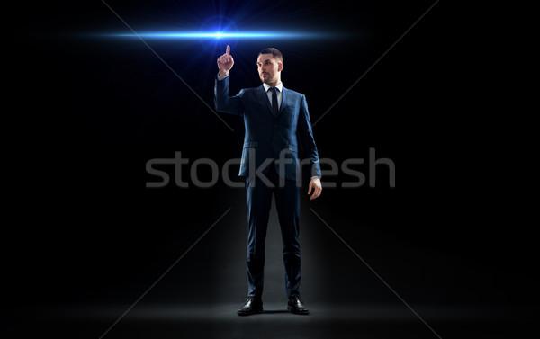 Imprenditore suit punta dito laser luce Foto d'archivio © dolgachov