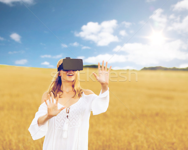 woman in virtual reality headset on cereal field Stock photo © dolgachov