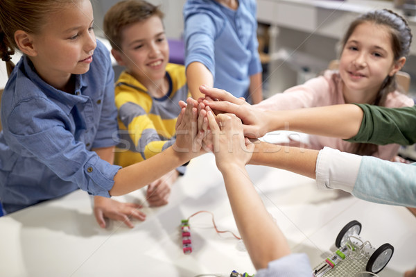happy children making high five at robotics school Stock photo © dolgachov