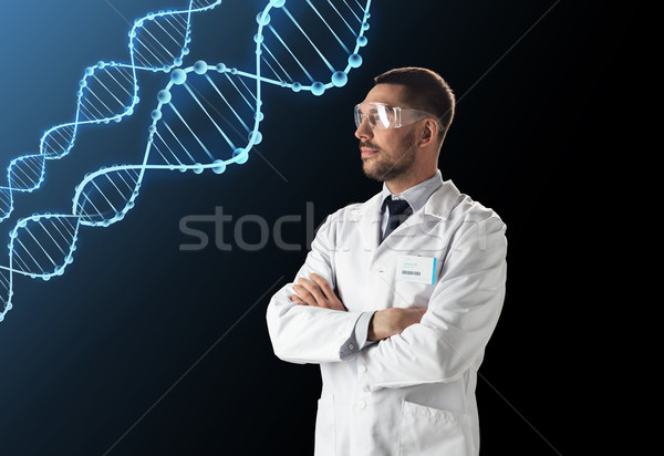 scientist in lab coat and safety glasses with dna Stock photo © dolgachov