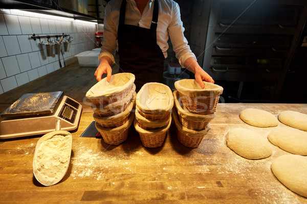 baker with baskets for bread dough at bakery Stock photo © dolgachov