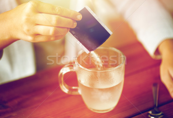 Stock photo: woman pouring medication into cup of water