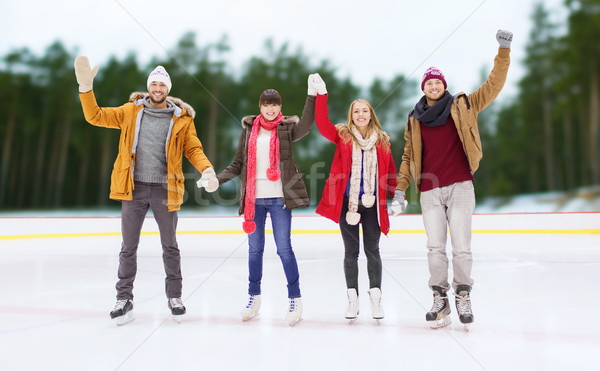 happy friends waving hands on outdoor skating rink Stock photo © dolgachov