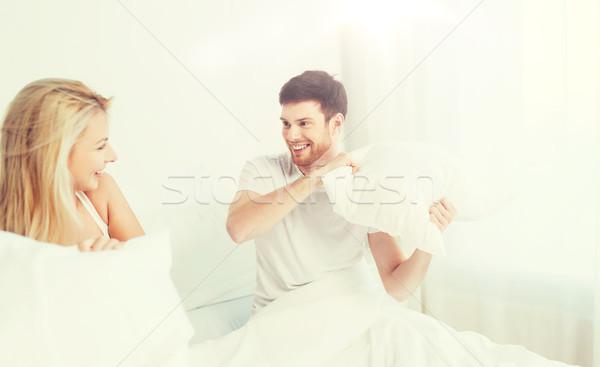 Heureux couple bataille d'oreillers lit maison personnes Photo stock © dolgachov