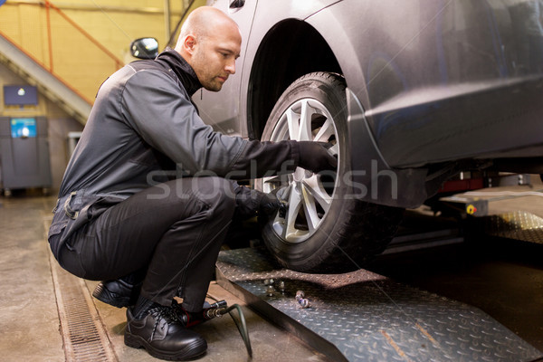 auto mechanic changing car tire at workshop Stock photo © dolgachov