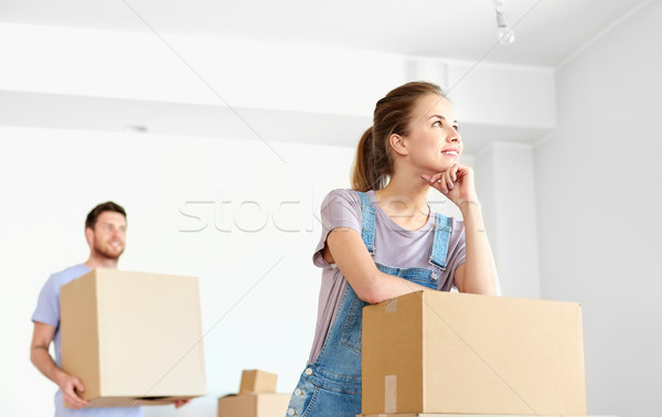 happy couple with boxes moving to new home Stock photo © dolgachov
