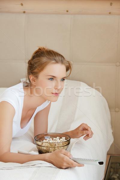 happy teenage girl with TV remote and popcorn Stock photo © dolgachov