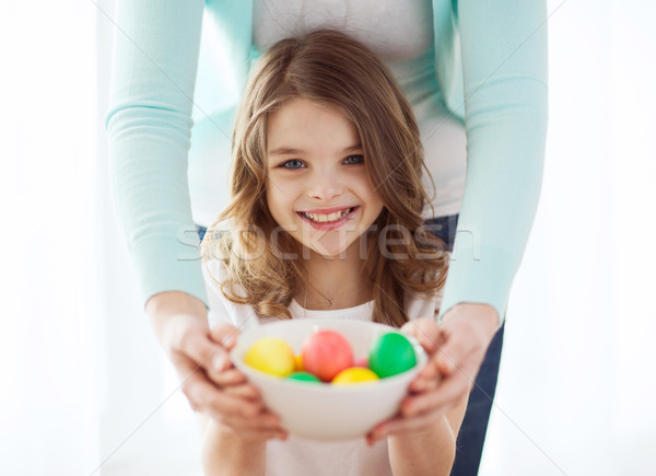 smiling girl and mother holding colored eggs Stock photo © dolgachov