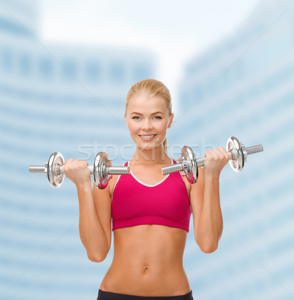 smiling woman lifting steel dumbbells Stock photo © dolgachov