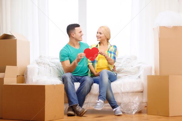 Mosolyog pár piros szív kanapé új otthon Stock fotó © dolgachov