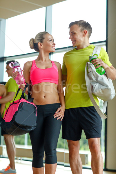smiling couple with water bottles in gym Stock photo © dolgachov