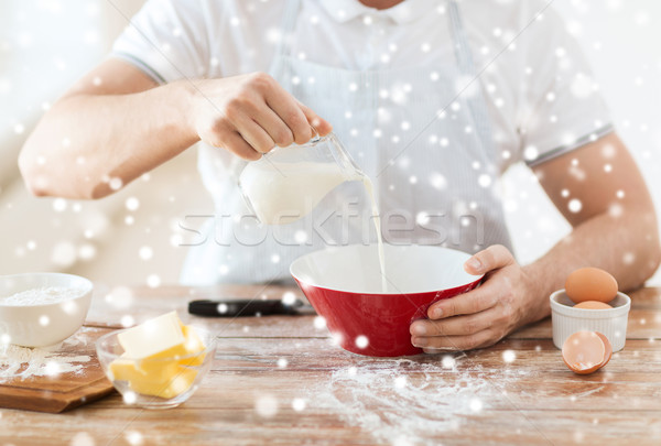 close up of man pouring milk into bowl Stock photo © dolgachov