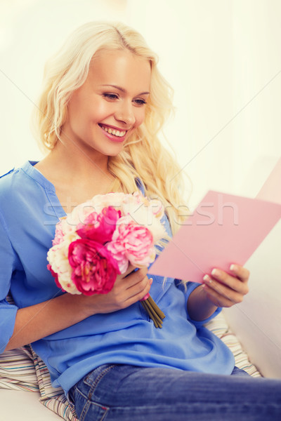smiling woman with card and bouquet of flowers Stock photo © dolgachov