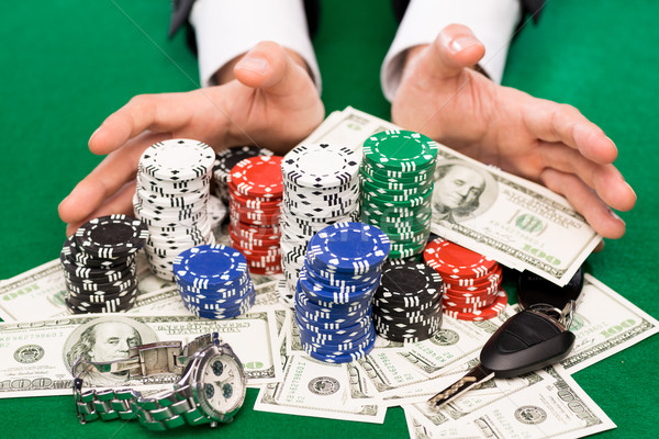 poker player with chips and money at casino table Stock photo © dolgachov