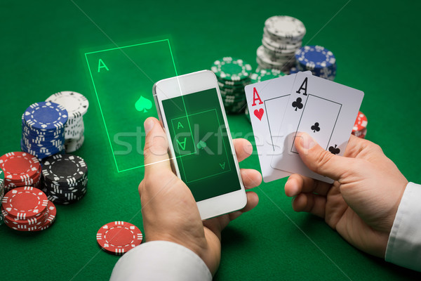 casino player with cards, smartphone and chips Stock photo © dolgachov