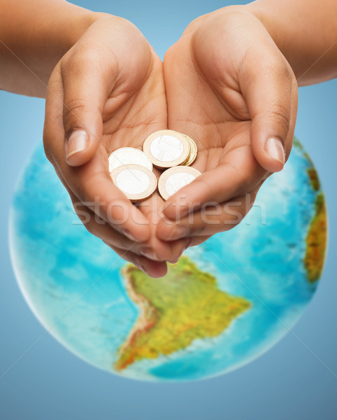 cupped hands holding euro coins over earth globe Stock photo © dolgachov