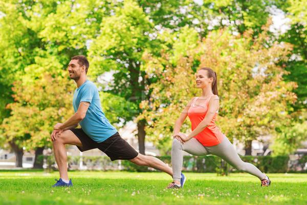 smiling couple stretching outdoors Stock photo © dolgachov