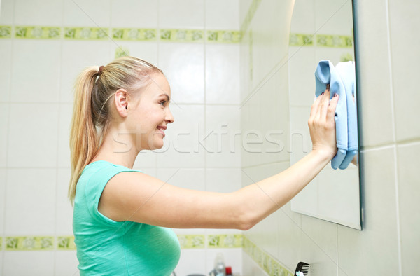 happy woman cleaning mirror with rag Stock photo © dolgachov