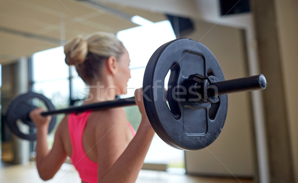 happy woman flexing muscles with barbell in gym Stock photo © dolgachov