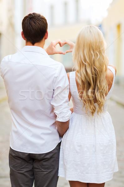 romantic couple in the city making heart shape Stock photo © dolgachov