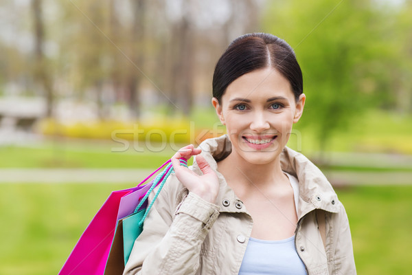 smiling woman with shopping bags coming from sale Stock photo © dolgachov